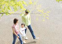 新緑の公園を散歩する親子3人