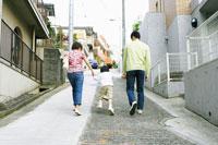 住宅街の坂道を上る親子3人