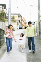 住宅街の坂道を下る親子3人
