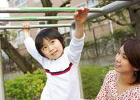 公園のうんていで遊ぶ男の子とお母さん