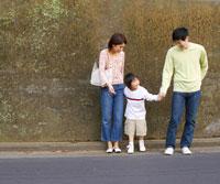 手を繋いで並ぶ親子3人