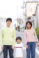 住宅街で手を繋ぐ親子3人のポートレート
