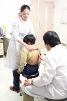 男の子の背中に聴診器をあてる医師