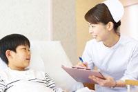 ベッドの男の子と笑顔で会話をする女性看護師