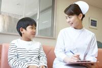 ロビーのソファーに座る男の子と女性看護師