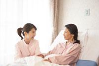 患者の手を握る女性介護士