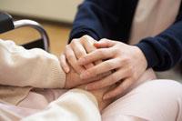 車いすの患者の手を握る女性介護士