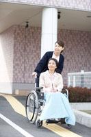 女性の患者の車いすを押す女性介護士