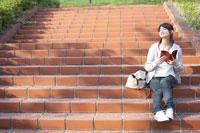 公園の階段に腰をおろし読書をする女子大生