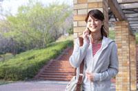 公園の柱にもたれ携帯電話をかける20代女性