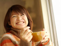 窓辺でスープを飲む20代女性
