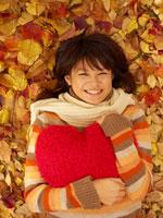 赤いクッションを抱いて落ち葉に寝転ぶ20代女性