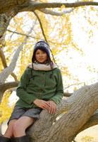 木にもたれる白いマフラーを巻いた20代女性