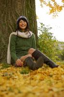 落ち葉に腰をおろす白いマフラーを巻いた女性