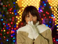 クリスマスネオンの前に立つ白いマフラーを巻いた女性