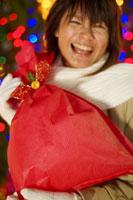 赤いラッピングのプレゼントを抱いた20代女性