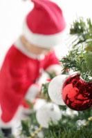 クリスマスツリーとサンタクロースの衣装を着た赤ちゃん