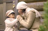 ログハウスの入り口に座るお母さんと女の子