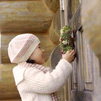 ログハウスのドアにクリスマスリースを付ける女の子