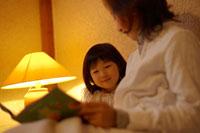 お母さんにベットで本を読んでもらう女の子