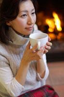 暖炉の前でコーヒーを飲む30代女性