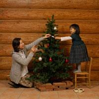 クリスマスツリーの飾り付けをするお母さんと女の子