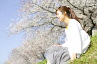 桜の前で座る女性