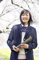 桜並木の前に立つ女子学生
