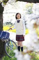 桜の前に自転車と立つ女子中学生