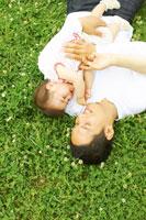 芝生の上で寝転がる父と赤ちゃん