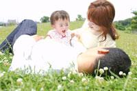 芝生の上で寝転がる家族