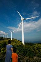 風力発電の前に立つ母と子