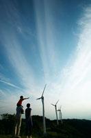 風力発電の前に立つ家族