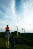 風力発電の前で肩車する父と子