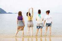 砂浜に立つ4人の女の子の後姿