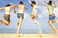 砂浜でジャンプする4人の女の子