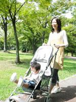 ベビーカーで公園を散歩する母子