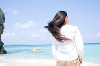 波打ち際に立つ女性の後ろ姿