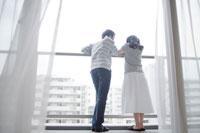 マンションのベランダでくつろぐ夫婦 02336005031| 写真素材・ストックフォト・画像・イラスト素材|アマナイメージズ