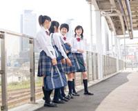 駅のホームで立っている女子高校生