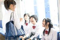 電車の中で話をする女子高校生