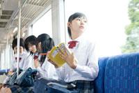 電車の中で勉強する女子高校生
