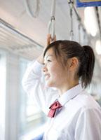 電車の窓から外を眺める女子高校生