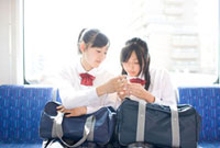 電車で話をする女子高校生