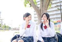 ベンチに座ってアイスを食べる女子高校生