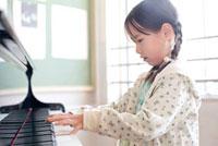 ピアノを弾いている小学生の女の子