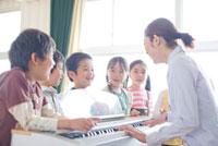 ピアノを囲んで歌っている先生と小学生