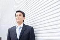 白い壁の前で立っているビジネスマン