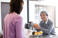 キッチンで料理をしているシニア女性と座っているシニア男性 02336005361| 写真素材・ストックフォト・画像・イラスト素材|アマナイメージズ