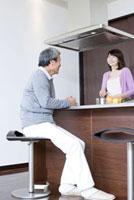 キッチンで料理をしているシニア女性と座っているシニア男性